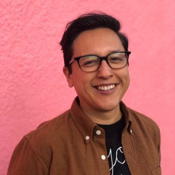 nat ruiz tofano headshot Image description: A close-up of a Mexican and Chinese person with medium brown skin and short black hair, smiling at the camera. They are wearing a black rimmed glasses and a brown collared shirt over a black t-shirt.
