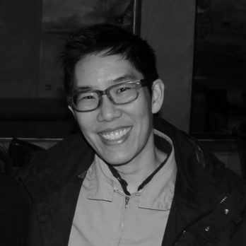 A black and white close-up photo of a Chinese American nonbinary trans person with short black hair, smiling at the camera. They are wearing a light collared shirt underneath a puffy black jacket.