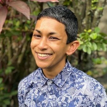 A South Asian nonbinary person with medium brown skin and short black and gray hair, smiling at the camera. They are wearing a short-sleeved collared shirt with a blue and white floral pattern. Behind them is a gray brick wall and leafy green and red plants.