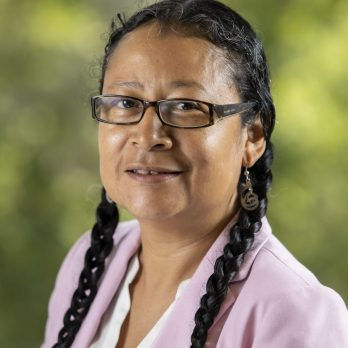 A Náhuat/Salvadoran woman with medium brown skin and long black hair in two braids, smiling at the camera. She is wearing dark framed glasses, a white shirt, and a light pink blazer.